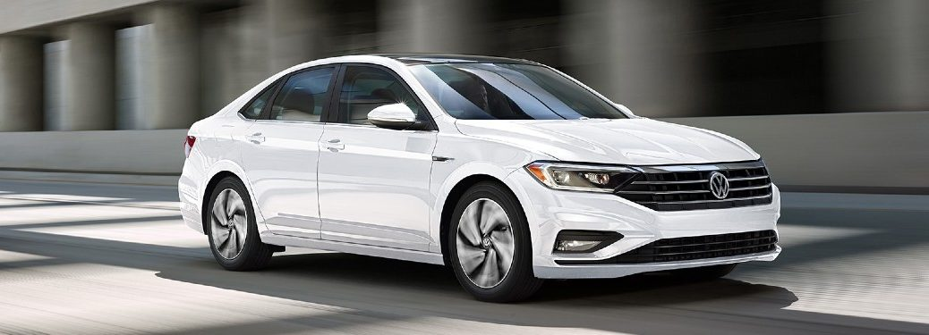 Front passenger angle of a white 2020 Volkswagen Jetta driving on a road
