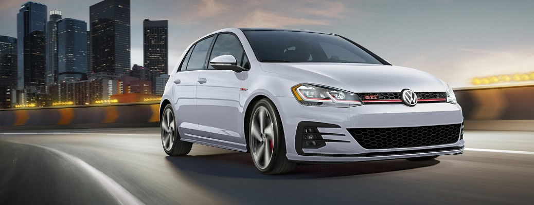 2020 Volkswagen Golf GTI exterior shot with white paint color driving on a highway at night