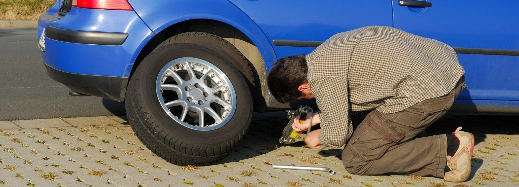 Man changing a tire on his blue car