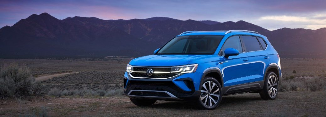 Front driver angle of a blue 2022 Volkswagen Taos with mountains in the background