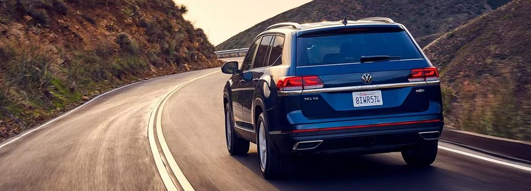 Rear driver angle of a blue 2021 Volkswagen Atlas driving on a road