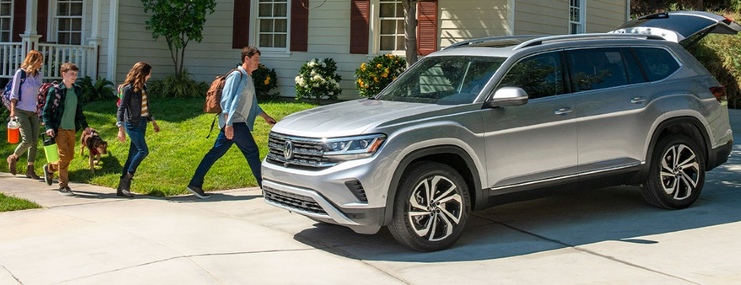 A family of four walking toward a 2021 Volkswagen Atlas that is sitting in a driveway right next to a house