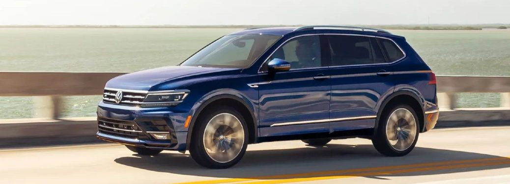 Front driver angle of a blue 2021 Volkswagen Tiguan driving on a road