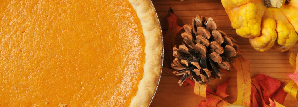 sweet potato pie shown with pine cone and squashes on a table for thanksgiving