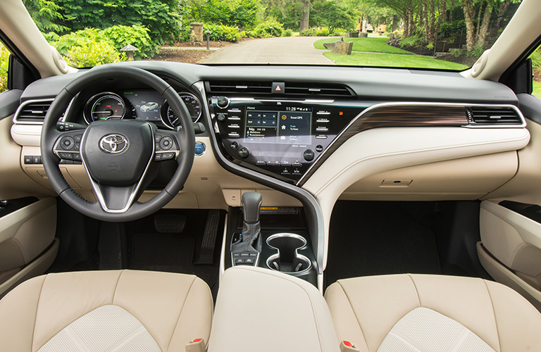 Interior view of a 2018 Toyota Camry Hybrid showing tan seating and steering wheel