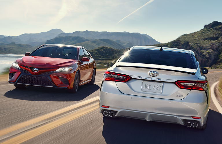 View of two 2018 Toyota Camry Hybrid models passing each other on a curved road with mountains in the background