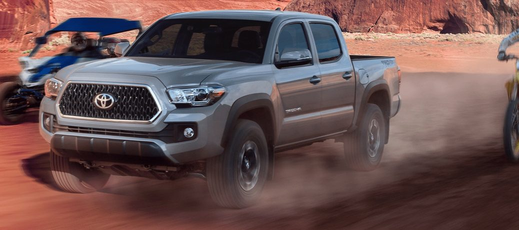 silver 2019 Toyota Tacoma by a motorcycle