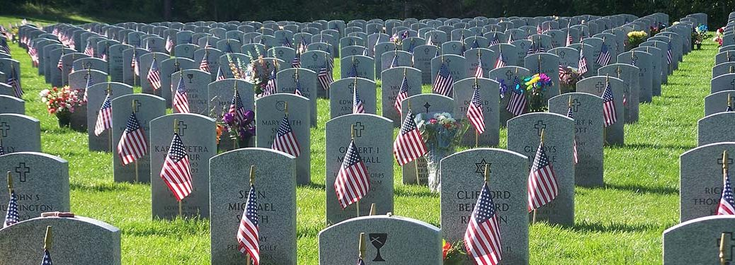 grave stones with flags and grass