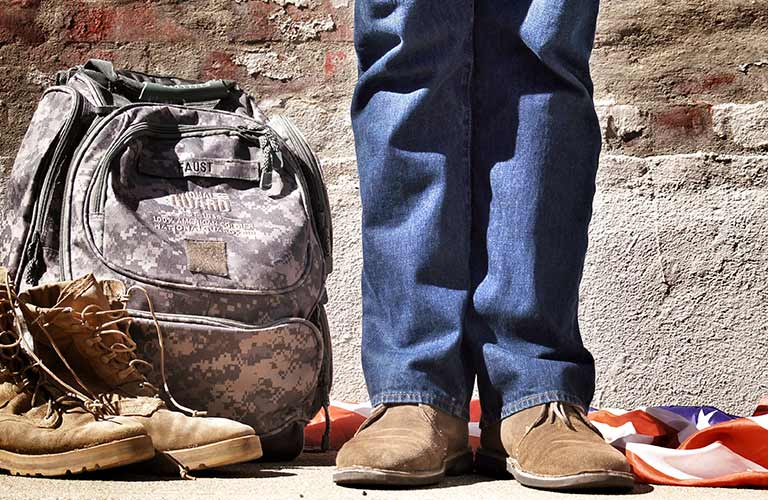 feet next to a backpack and flag