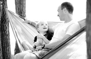 black and white photo of father and son in hammock
