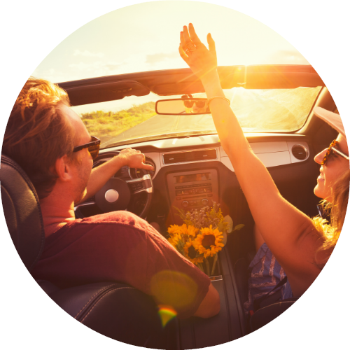 couple in front seat of convertible having fun in the sun