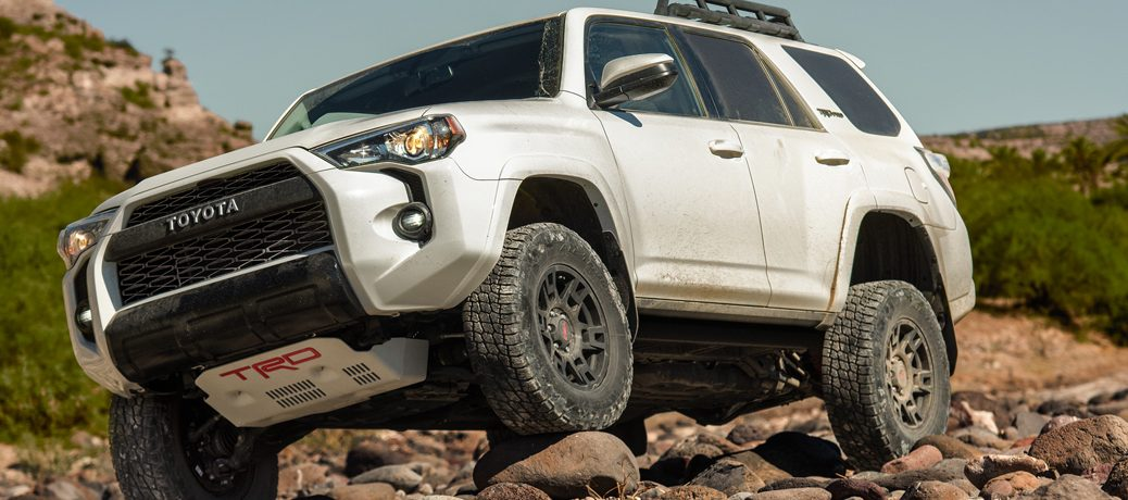 white 2019 Toyota 4Runner driving down rocks