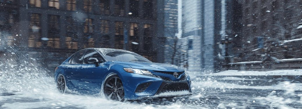 blue 2020 Toyota Camry driving through rain