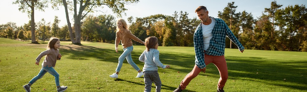 family playing tag in park