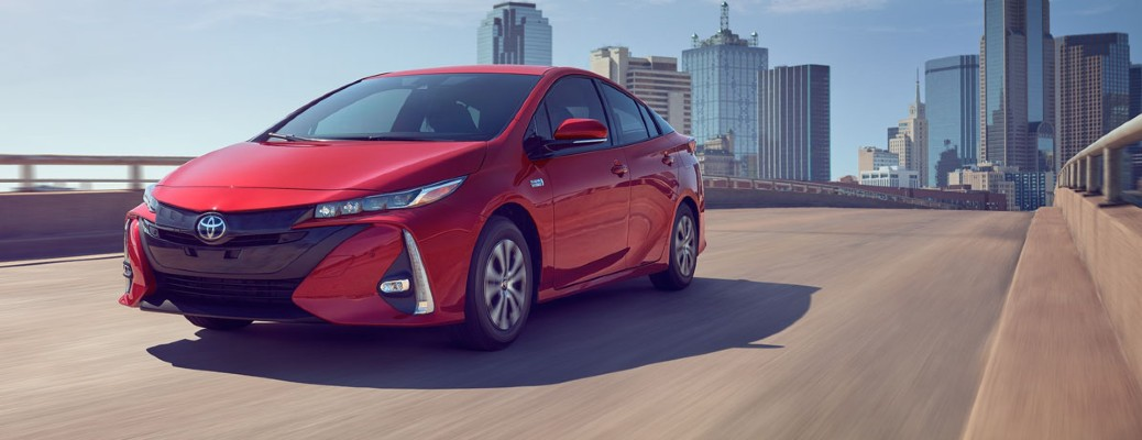 red 2020 Toyota Prius Prime driving away from city