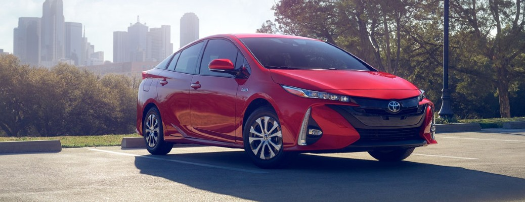 red 2020 Toyota Prius Prime driving through city