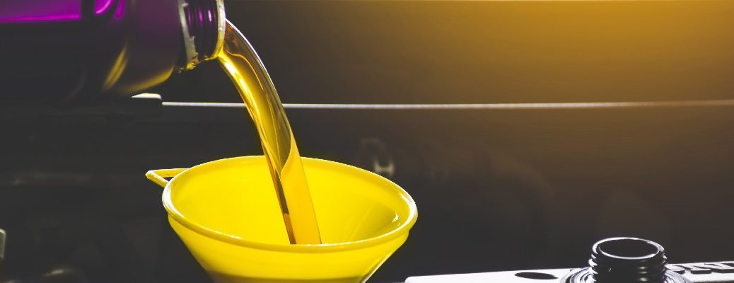 A stock photo of oil being poured into an engine.