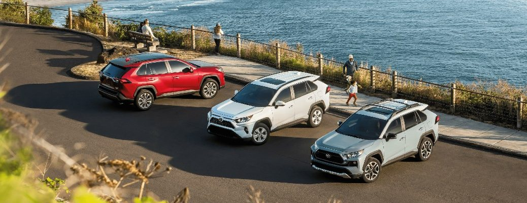 A trio of 2021 Toyota RAV4 models lined up by the ocean.