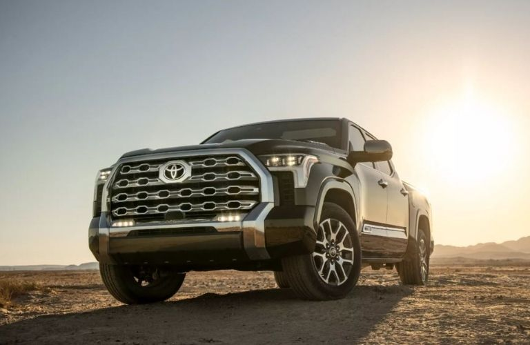 Front view of a black 2022 Toyota Tundra parked in a desert with the sun in the background