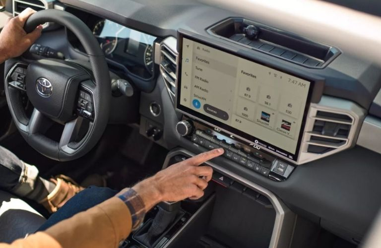 A man's hand seen some pressing buttons below the big touchscreen infotainment display inside the 2022 Toyota Tundra