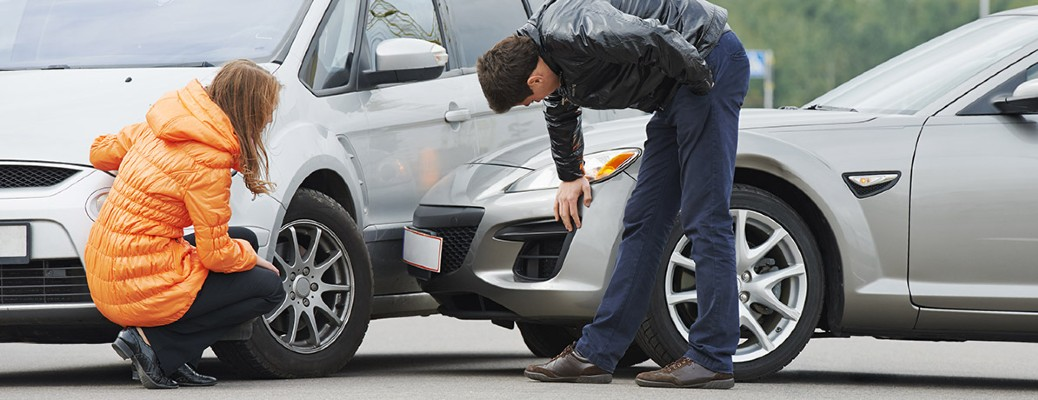 two people examining two cars