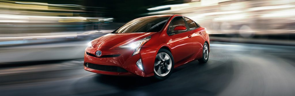 Red Toyota Prius driving down street