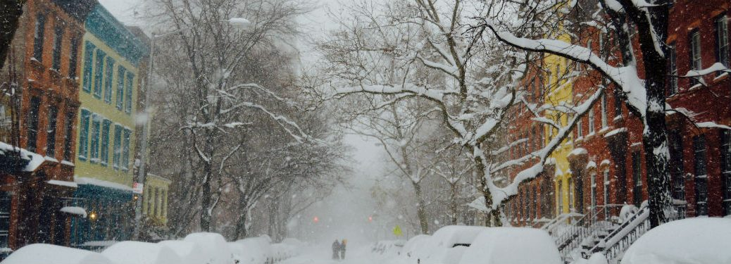 snow covered street and trees buildings on side people walking