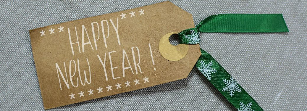 gift tag with happy new year on it and green ribbon