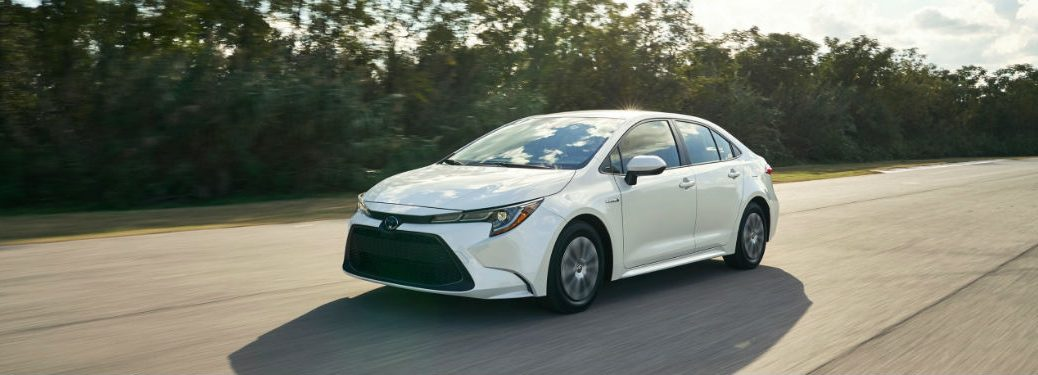 2020 Toyota Corolla white exterior front fascia driver side driving on tree lined road