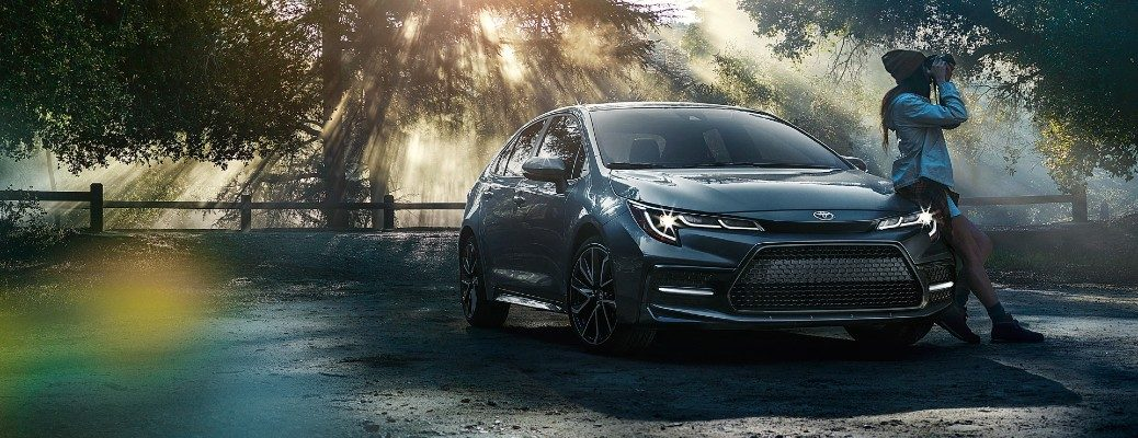 2020 Toyota Corolla dark paint parked in park with woman leaning on front of car