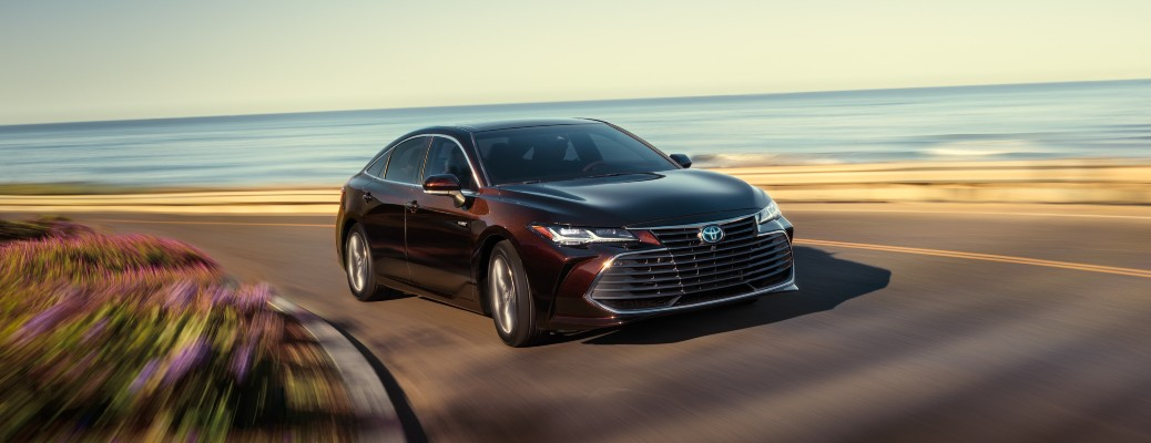 2020 Toyota Avalon Limited dark red color driving around curve with water in background