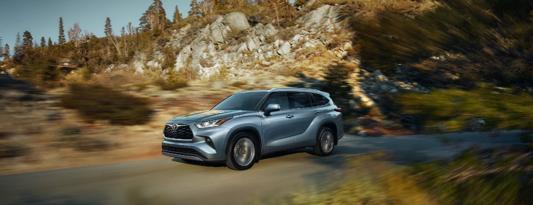 2020 Toyota Highlander driving on road through hills with motion blur
