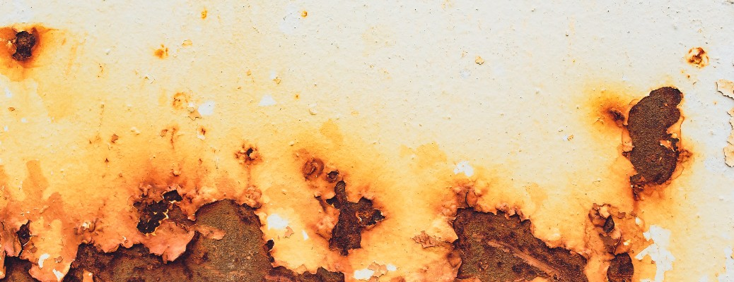 stock photo of rusted side of car peeling off white paint