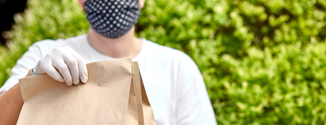 Person with mask and gloves handing over folded paper bags