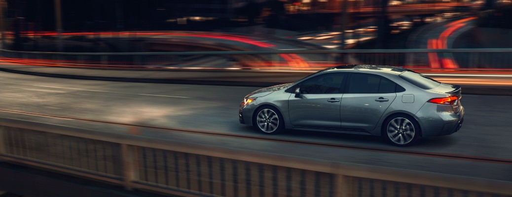 2021 Toyota Corolla driving on night bridge with red lights in background