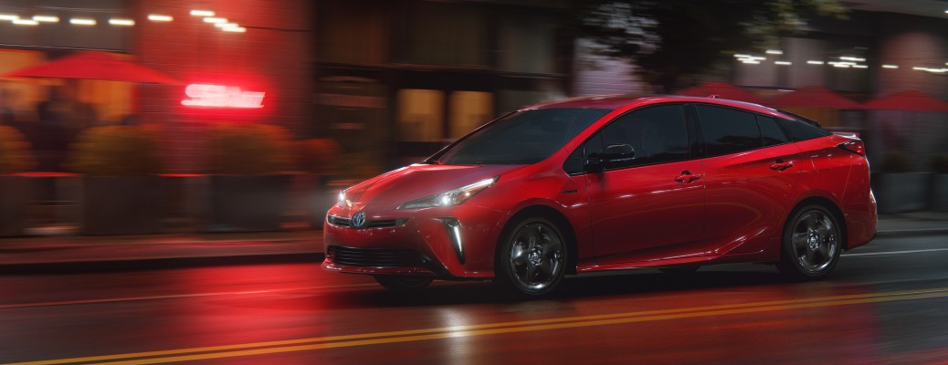 2021 Toyota Prius supersonic red 2020 edition driving to the left past red neon light