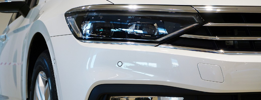 close up of front end of car grille and headlight with sensors
