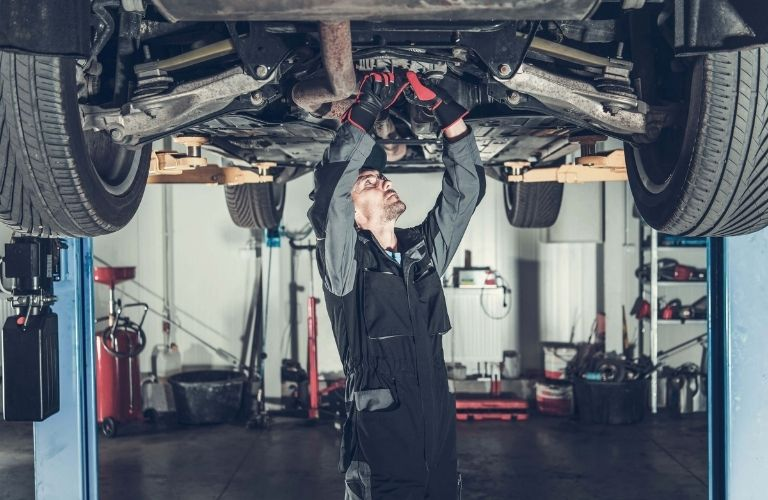 Toyota mechanic checking the level of a car engine oil