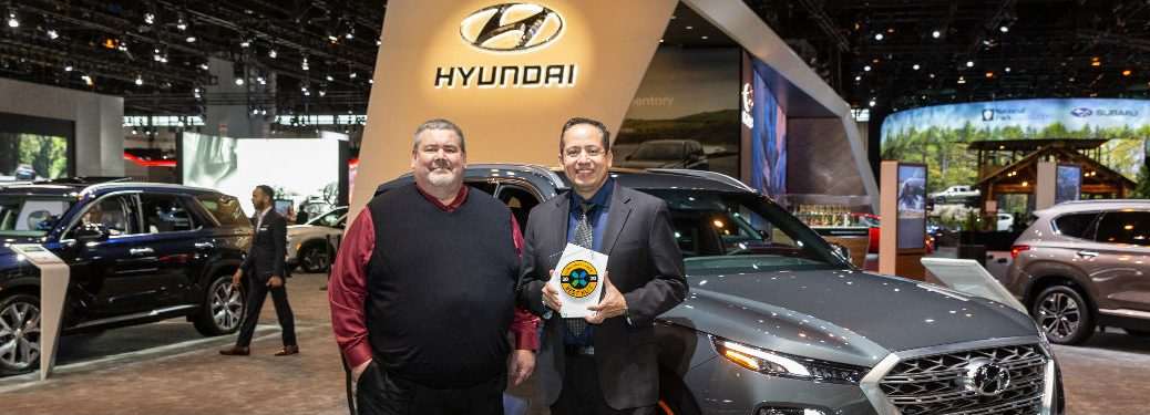Two men standing in front of a Hyundai