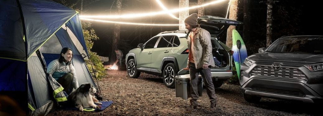 Couple with Two 2020 Toyota RAV4 Models on a Campsite at Night
