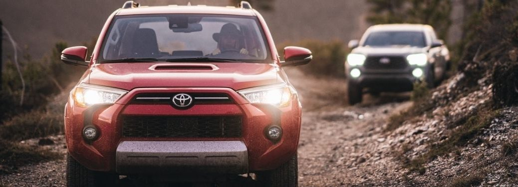 Red 2021 Toyota 4Runner and Gray 2021 Toyota Tacoma on a Trail