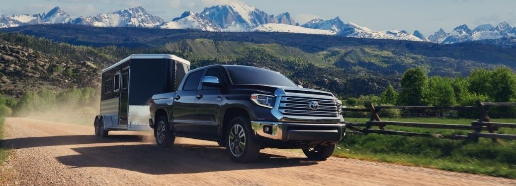 Black 2021 Toyota Tundra Towing a Trailer on a Country Road