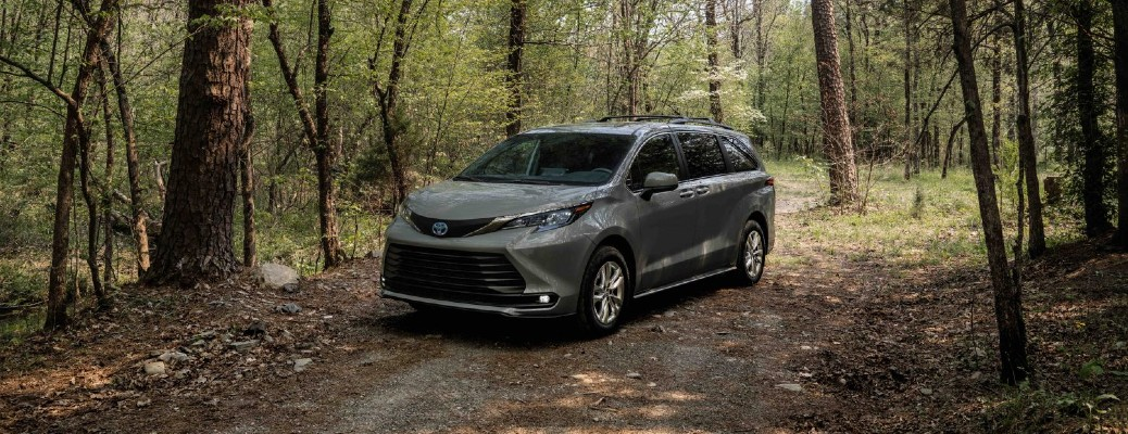 The front and side view of a Cement Gray 2022 Toyota Sienna Woodland Special Edition parked under a set of trees on a trail.