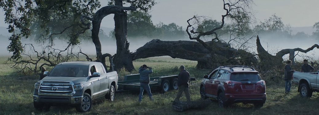 """snapshot from toyota's """"r+s"""" commercial featuring multiple toyota trucks helping cut down tree"""