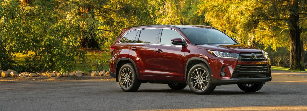 red 2018 toyota highlander in front of green and yellow trees