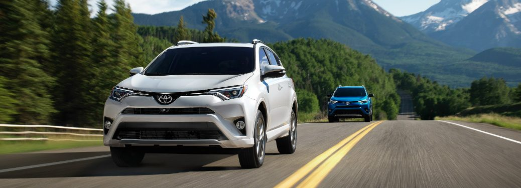 white 2018 toyota rav4 hybrid followed by blue rav4 driving on highway with mountains in background