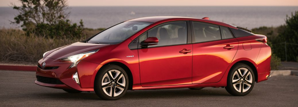 red 2018 toyota prius with ocean behind it