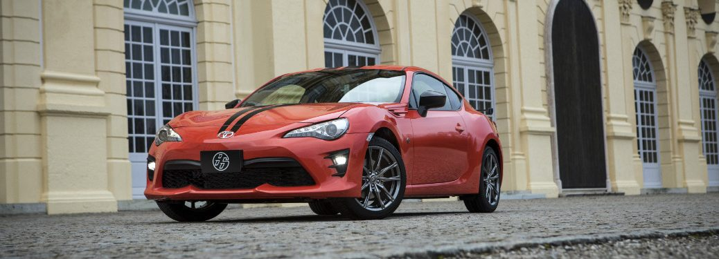 orange and black 2018 toyota 86 in front of old white brick building
