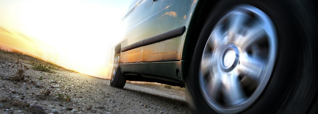 generic car tire driving on asphalt road with sun behind it