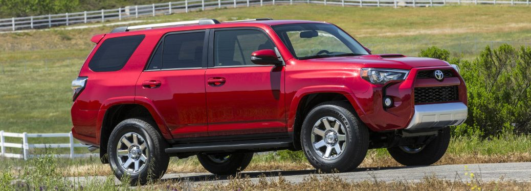 red 2018 toyota 4runner driving on farm road surrounded by grass